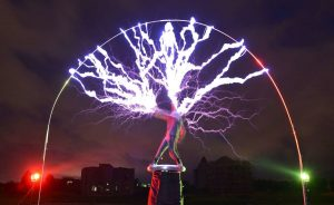 """The guitarist of the band """"Lightningfan"""" Wang Hongbin (C) creates lightning with a Tesla Coil in their village outside of Fuzhou in China's Fujian province on June 24, 2013. The Tesla Coil invented by Nikola Tesla in 1891 is a transformer that produces vast amounts of voltage at high frequencies that creates long bolts of electricity like lightening. Inventor and founding member of the band Wang Zengxiang, an electrical engineer made his first Tesla Coil in 2007 and afterwards formed his 10 member band who, whilst wearing ferroalloy metal suits play guitars, violins and drums with bolts of lightening crackling from them and their instruments to the beat. AFP PHOTO/Peter PARKSPETER PARKS/AFP/Getty Images"""